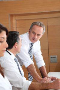Delegating_business man speaking to team member