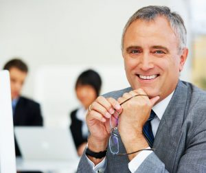 Relaunching After 50 - older business man holding glasses