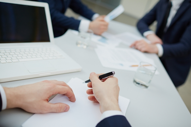 Image of human hands with pen writing business plan
