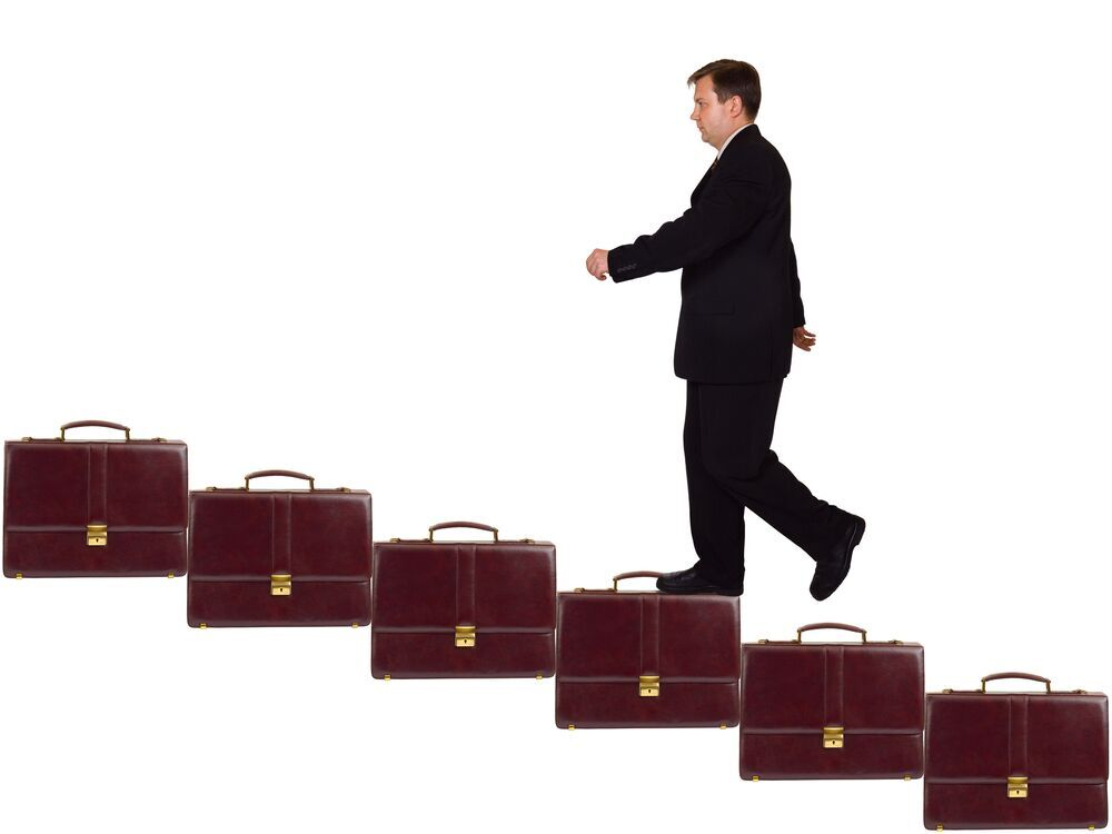 Promotion Advice - Man climbing ladder of suitcases
