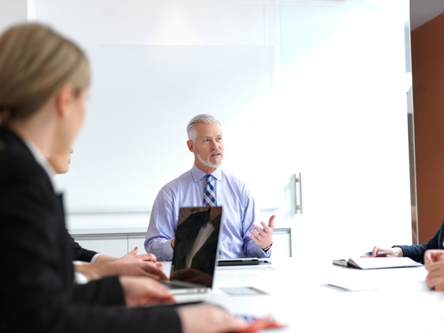 Chief Brand Officer - business people at conference table with laptop