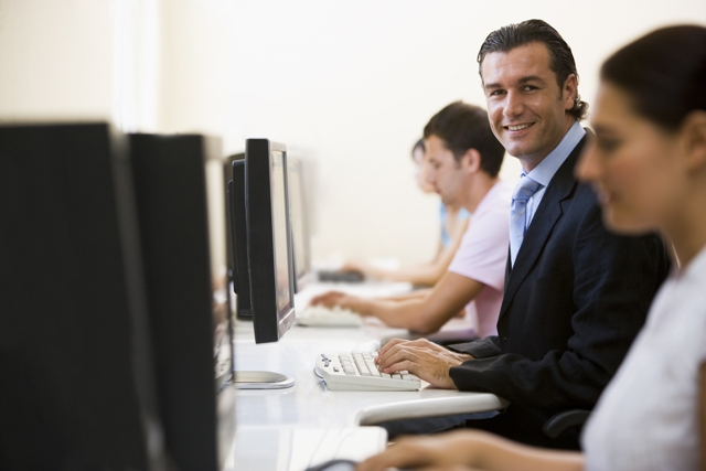 Core Competencies - employees at desktop computer - man smiling