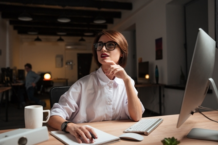 Happy pensive young businesswoman in glasses thinking and working in office