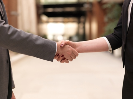 business partners concept with businessman and businesswoman handshake at modern office indoors