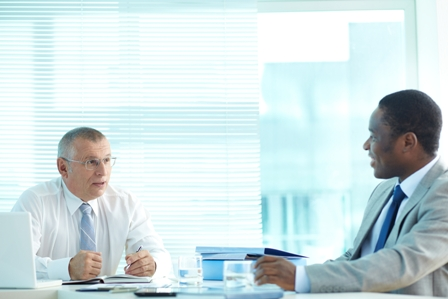 Portrait of senior boss and his employee talking at meeting
