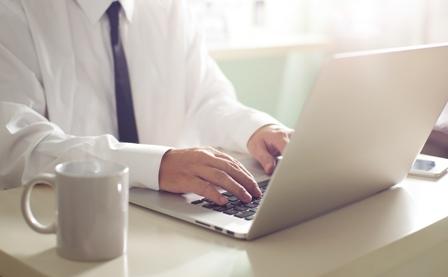Businessman hands working on laptop,Blurred background .