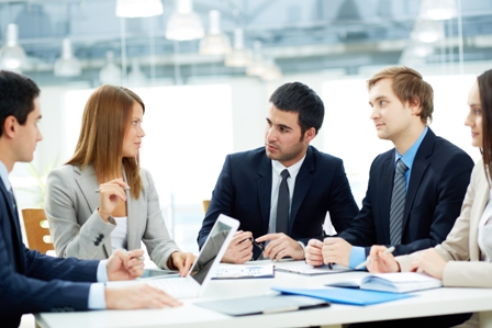 Image of business partners listening to female employee at meeting