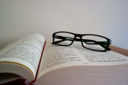 Mental Resources - Textbook with black-rimmed glasses