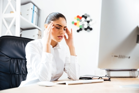 Tired businesswoman having a headache while sitting at the office desk