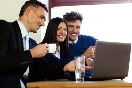 Determining-Company-Culture-During-Job-Interview-Smiling-Employees-at-Laptop-Computer