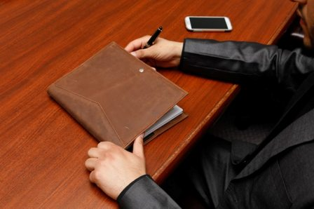 Yearly Business Review Advice - Exec with portfolio at table