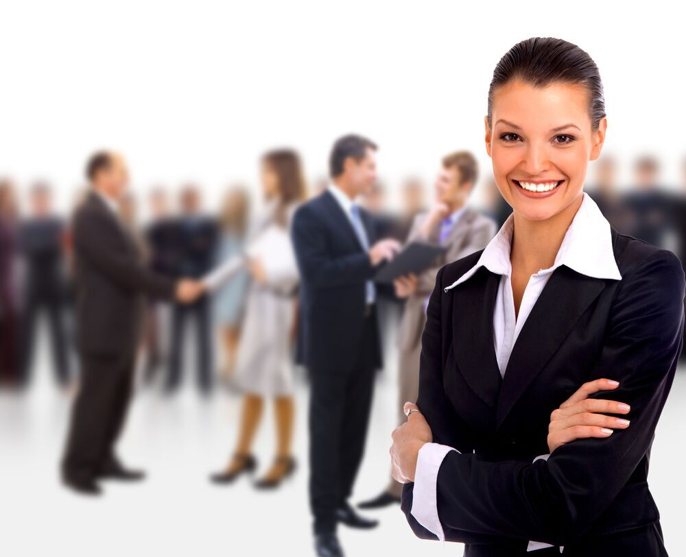 Emotional Intelligence - Smiling business woman with working staff in background