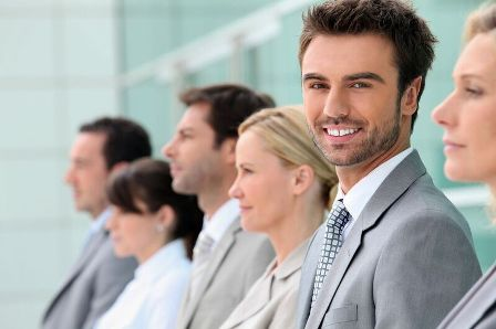 Simple recruiting tips - Young male employee standing among other professionals