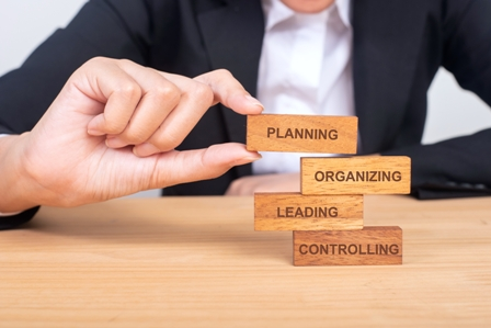 Organizational Development concept - executive placing building blocks on desk