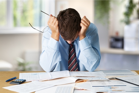 Tired young businessman holding glasses - looking down at papers