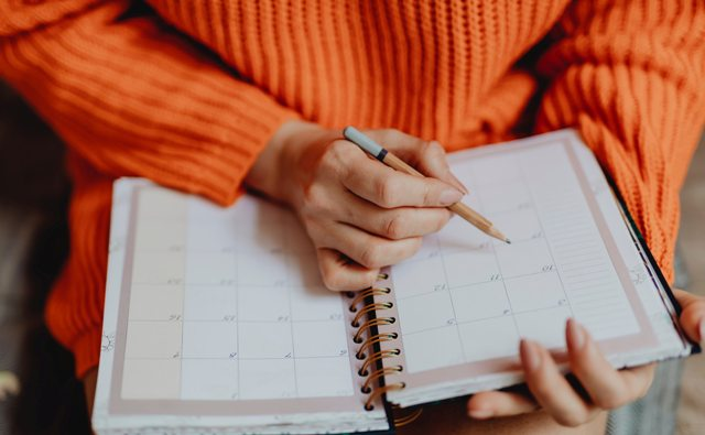 Job Search - woman in orange sweater writing in calendar